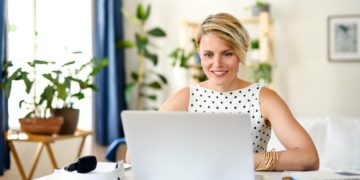 Cheerful young businesswoman with laptop indoors in home office, working